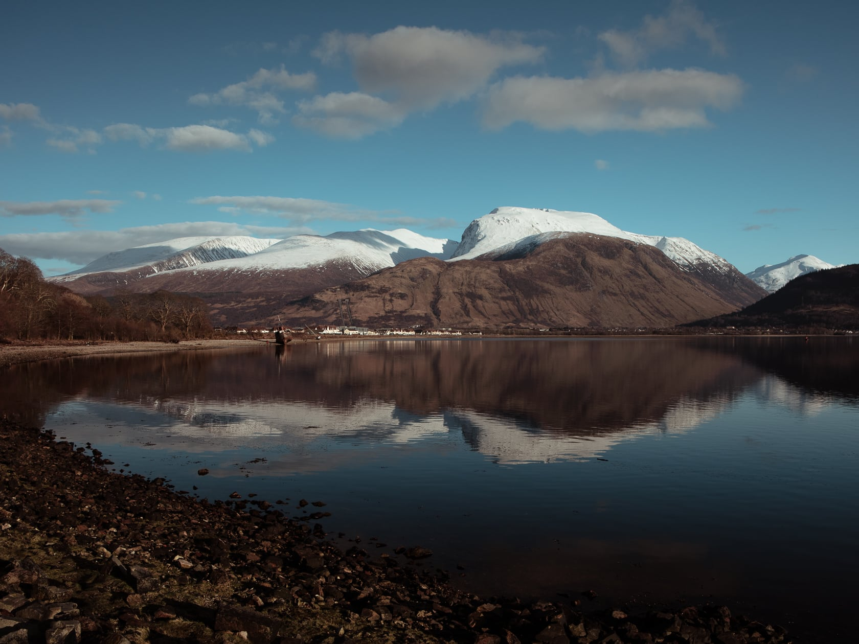 ben nevis with snow on top reflected on the loch water in winter