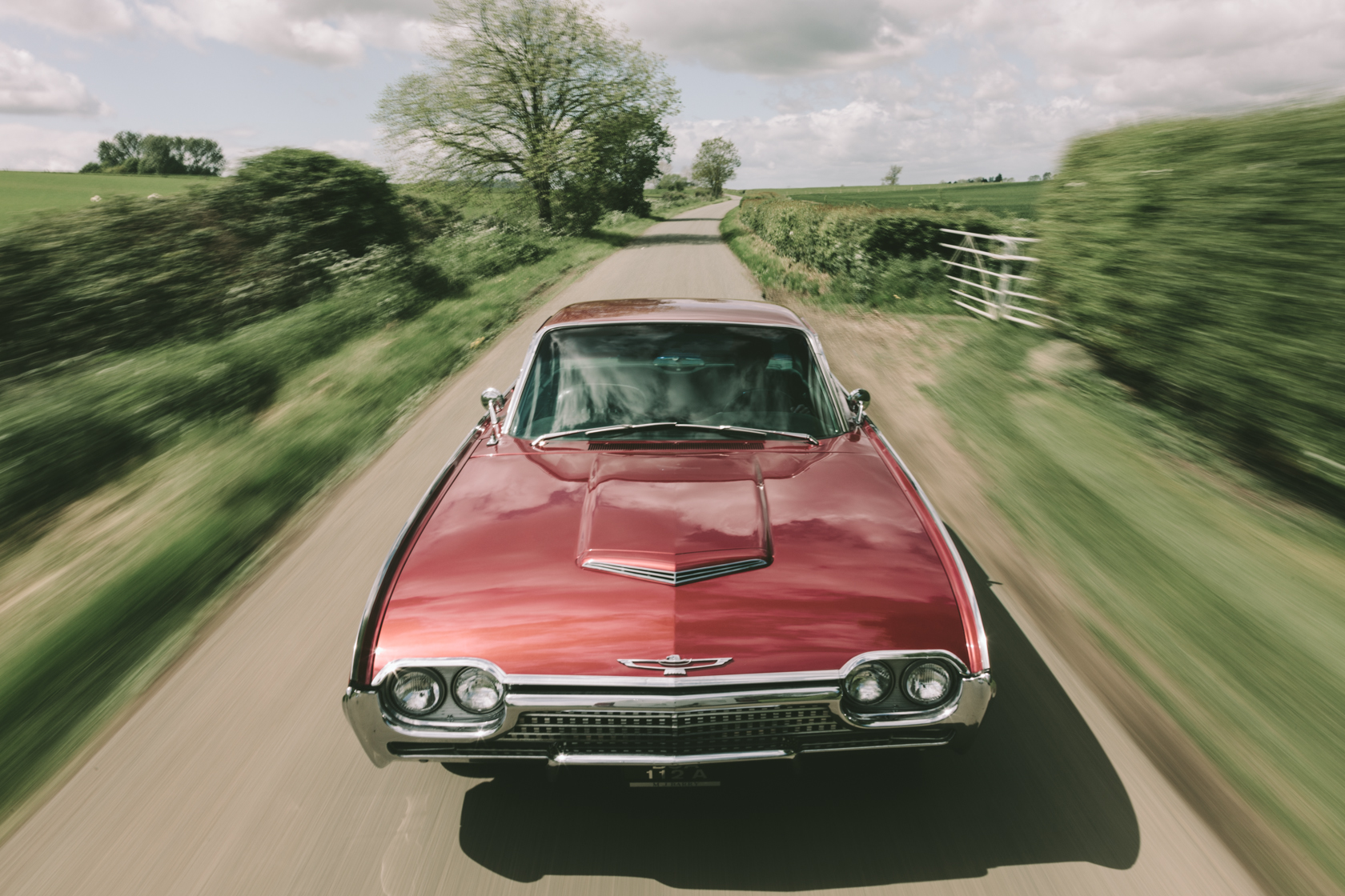 cherry red ford thunderbird driving through countryside