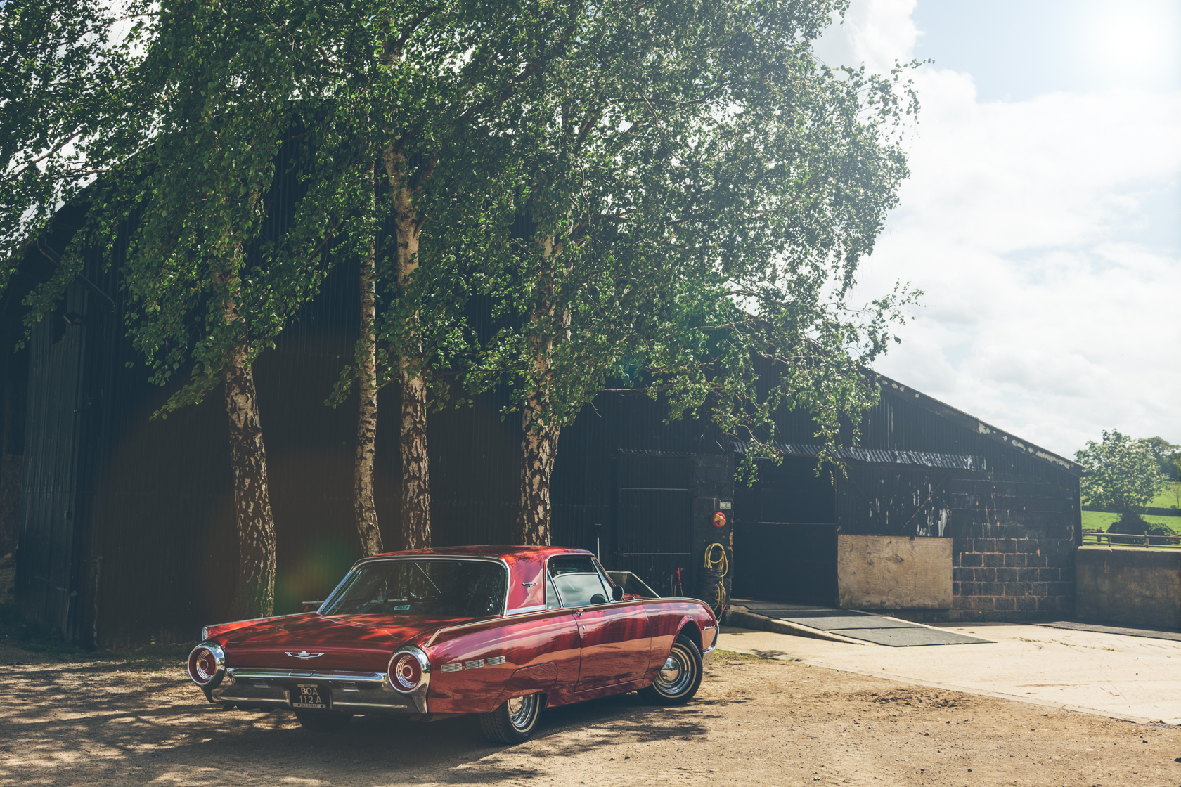 red classic ford thunderbird next to a black barn